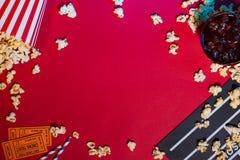Filmkarten, clapperboard, Popcorn auf rotem Hintergrund stockbild