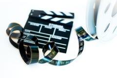 Filmklep en de uitstekende 35 mm-spoel van de filmbioskoop op wit Stock Afbeeldingen
