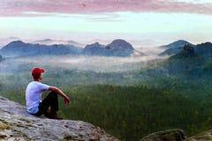 Filmkorn Erwachsener Sportler im weißen Hemd, in den dunklen trousars und in der roten Kappe Mann sitzen auf scharfer Klippe Stockfoto