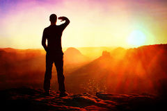 Filmkorn Ung idrottsman som skuggar hans ögon från det ljusa ljuset av gryningsolen Arkivbilder