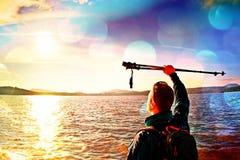 Filmkorrel Mens met polen boven hoofd De korte toerist van het gemberhaar in blauwe kleding en rugzak met hand stock foto