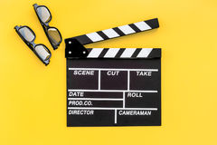 Filmmaker accessories. Clapperboard and glasses on yellow background top view.  Royalty Free Stock Photography
