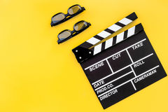 Filmmaker accessories. Clapperboard and glasses on yellow background top view copyspace. Filmmaker accessories. Clapperboard and glasses on yellow background top Royalty Free Stock Image