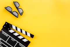 Filmmaker accessories. Clapperboard and glasses on yellow background top view copyspace. Filmmaker accessories. Clapperboard and glasses on yellow background top Stock Photos