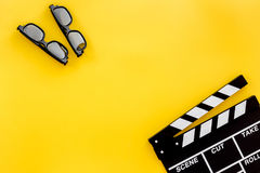 Filmmaker accessories. Clapperboard and glasses on yellow background top view copyspace. Filmmaker accessories. Clapperboard and glasses on yellow background top Royalty Free Stock Photography