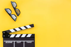 Filmmaker accessories. Clapperboard and glasses on yellow background top view copyspace. Filmmaker accessories. Clapperboard and glasses on yellow background top Stock Photo