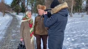 Filmmaker het lopen met bejaard paar en maakt een video Romantisch hoger paar walkink in het park in de wintertijd stock videobeelden