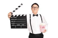 Filmregisseur, der ein clapperboard und ein Popcorn hält stockfoto