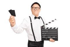 Filmregisseur, der ein clapperboard und zwei Karten hält stockbilder