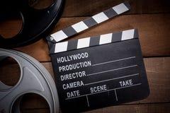 Filmrolle und Schindel Hollywood, Unterhaltungsindustriehintergrund auf einer h?lzernen Tabelle lizenzfreies stockbild