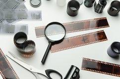 Filmrullar, negationer och förstoringsglas på vit bakgrund arkivbilder