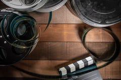 Filmrulle och panelbr?da Hollywood underh?llningsindustribakgrund p? en tr?tabell royaltyfri fotografi