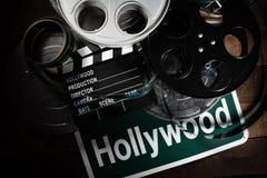 Filmrulle och panelbr?da Hollywood underh?llningsindustribakgrund p? en tr?tabell arkivbild
