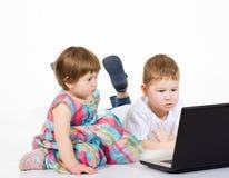 Films de bande dessinée de regard d'enfants sur l'ordinateur portable Photographie stock libre de droits