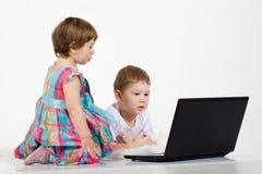 Films de bande dessinée de regard d'enfants sur l'ordinateur portable Image libre de droits