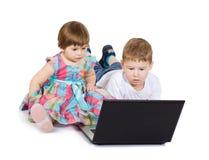 Films de bande dessinée de regard d'enfants sur l'ordinateur portable Images libres de droits