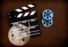 Filmscharnierventilbrett und Blau farbige Filmrollen Lizenzfreie Stockbilder
