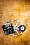 Filmscharnierventilbrett und -Filmrolle auf Bretterboden Stockfotografie