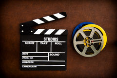 Filmscharnierventilbrett und -Filmrollen auf Bretterboden Stockfotografie
