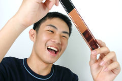 Filmstrip. Young asian guy looking at filmstrip Royalty Free Stock Image