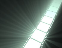 Filmstrip movie glowing light flare. Strip of video film negative projected with spotlight halo flares. Free space and emptied frame for message Royalty Free Stock Photo