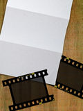 Filmstrip and paper. Paper and negative filmstrips on wood table Stock Image