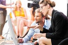 Filmteam, das Richtung für Videoproduktion bespricht Stockfotos