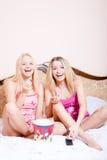 Filmtid: Två flickavänner eller blonda förtjusande attraktiva nätta unga kvinnor för systrar som sitter i säng med popcorn, hålla Arkivfoto