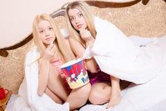 Filmtijd: 2 aantrekkelijke mooie de zusters jonge blonde mooie vrouwen die van meisjesvrienden in bed onder dekens met popcorn zi stock afbeeldingen