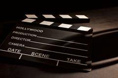 Filmu clapper z cieniem na drewnianym czarnym tle fotografia stock