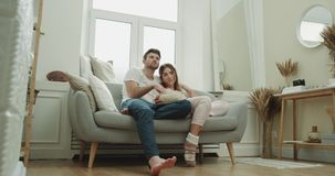 Filmu czas dla młodej pary wydaje dzień na kanapie w piżamach wpólnie są bardzo szczęśliwym łasowania popkornem 4K zdjęcie wideo