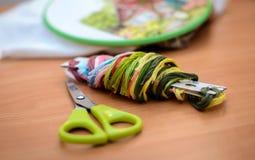 Filo colorato per ricamo e un paio di forbici sulla tavola Fotografia Stock Libera da Diritti