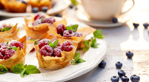 Filo cups with Mascarpone filling topped with raspberries on a white plate, delicious dessert royalty free stock photography