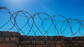 Filo di acciaio pungente su un recinto di pietra Immagine Stock