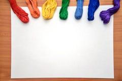 Filo di seta multicolore del ricamo su uno strato bianco Fotografie Stock