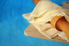 Filo dough and a rolling pin on a wooden board. On blue background Royalty Free Stock Images