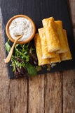 Filo rolls with meat, eggs and greens close-up and yogurt. Verti. Filo rolls with meat, eggs and greens close-up and yogurt on the table. Vertical view from Stock Photo