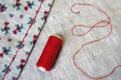 Filo rosso sopra tessuto di tela Fotografia Stock