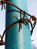 Filo spinato arrugginito intorno alla colonna ed al cielo blu d'acciaio dipinti Fotografie Stock