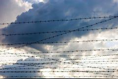 Filo spinato contro i precedenti del cielo nuvoloso Fotografie Stock Libere da Diritti