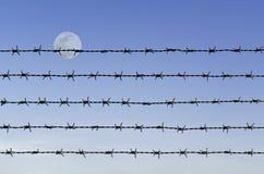Filo spinato sopra il cielo astratto della luna piena Fotografia Stock