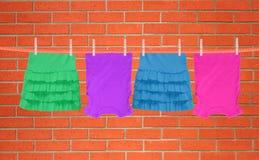 Filo stendibiancheria con i vestiti sopra il fondo del muro di mattoni Fotografia Stock Libera da Diritti