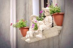 Filon-couche de fenêtre de balcon de pots de fleurs de fond d'enfants de statues de rebord de fenêtre Photo libre de droits