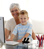 Fils à l'aide d'un ordinateur avec sa grand-mère photographie stock libre de droits