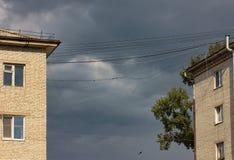 Fils électriques surplombants dangereusement, avant la tempête Image stock
