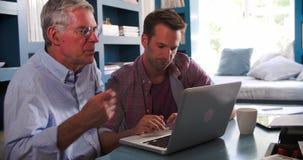 Fils aidant le parent supérieur avec l'ordinateur dans le siège social banque de vidéos
