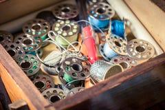 Fils, aiguilles et boutons dans la boîte en bois du ` s de tailleur Photos stock