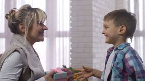 Fils aimant présent le boîte-cadeau à la mère étonnée