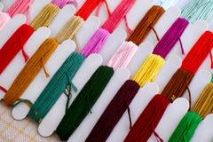 Fils colorés de broderie sur des bobines avec la toile prête pour le point croisé photos stock