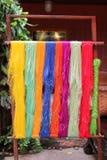 Fils colorés de plan rapproché en soie thaïlandais sur un tissu Photos stock